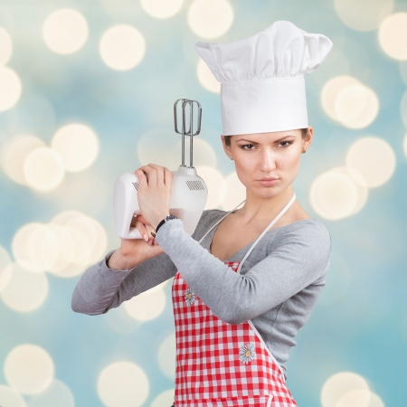 """Woman in chef s hat """"firing a gun"""" with the mixer, abstract blue background"""