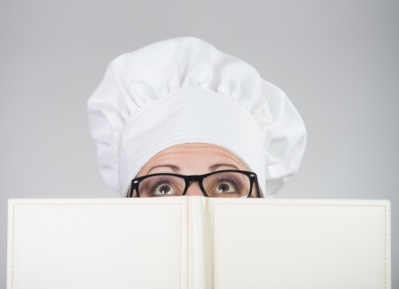 Woman in chef s hat looking over the cookbook, on grey background
