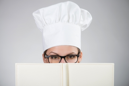 Closeup portrait of woman in chef s hat looking at camera over the cookbook on grey background
