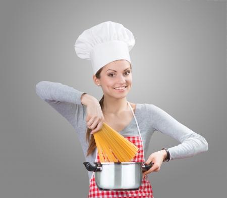 ama de casa: Retrato de una mujer sonriente en sombrero del cocinero s añadir la pasta a la olla, fondo gris