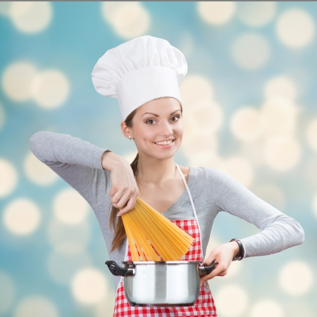 Portrait of a smiling woman in chef s hat adding the pasta to the pot on the blue abstract background photo