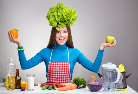 Happy woman with the salad on her head and with green apple and yellow sweet pepper in her hands