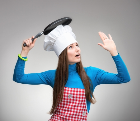 Young woman in chefs hat with the pan under her head looks up and raises her hand