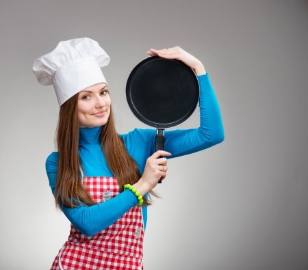 Portrait of a smiling pretty woman in chefs hat with the pan in her hands Stock Photo