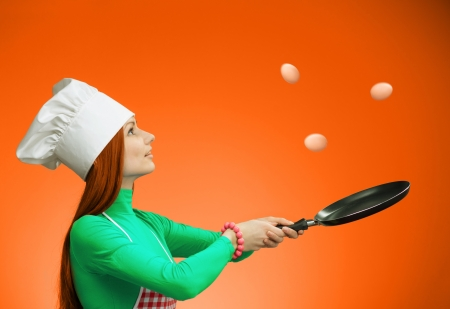 Woman in chefs hat throwing eggs in the air and catching it on the frying pan Stock Photo