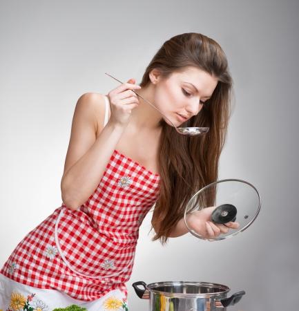 delantal: Mujer degustación de un plato con una cuchara sobre fondo gris Foto de archivo