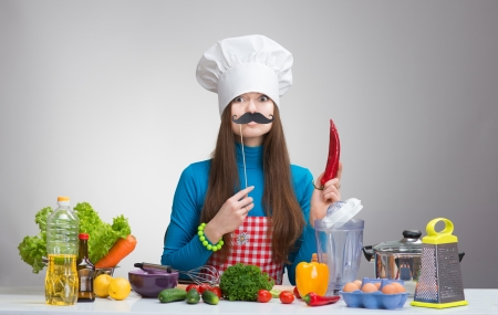 Humorous portrait of a woman in chef hat with paper mustache and the red pepper in her hand, on grey background