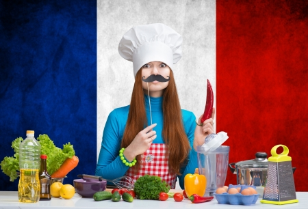 Humorous portrait of a female chef with paper mustache and the red pepper in her hand standing before a flag of France 写真素材