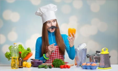 Humorous portrait of a woman in chef hat with paper mustache looking at the pepper in her hand Archivio Fotografico