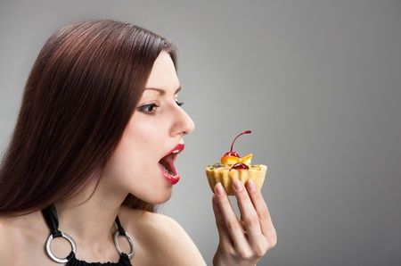 nibbling: Funny portrait of a woman nibbling the cake