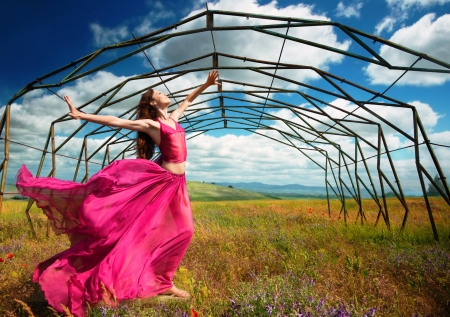 Outdoors portrait of a woman in airy crimson dress in front of the old metallic construction in windy spring day