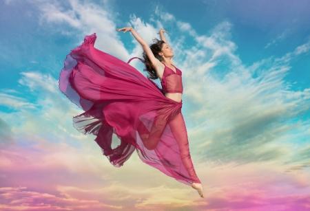 Vrouw in luchtige karmozijnrood jurk springen in de lucht bij zonsondergang Stockfoto