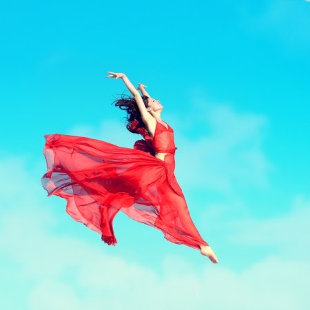 Woman in airy red dress jumping in the air, blue sky background