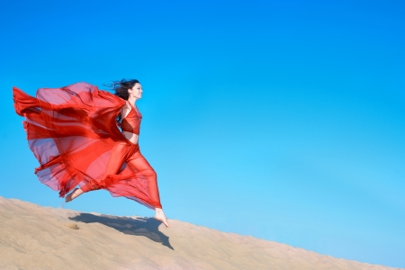 transparent dress: Woman in airy red dress running on sand dunes