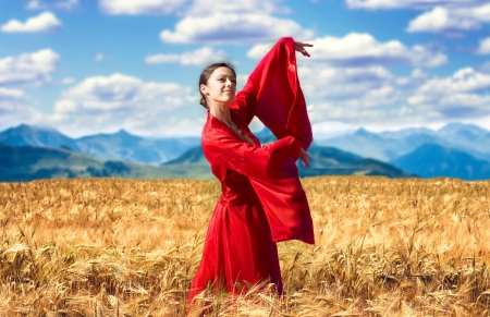 Portrait of a smiling woman in red clothes in the wheat field photo