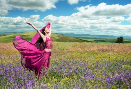 airy: Outdoors portrait of a woman in airy crimson dress posing in the blooming field in windy spring day