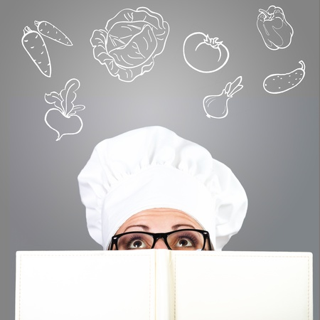 Woman in chef s hat looking over the cookbook, with the drawn ingredients on grey background Stock Photo