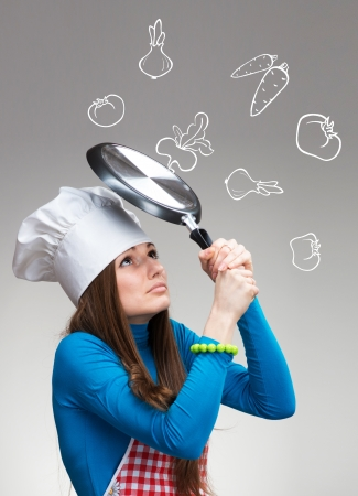 Woman with the pan protecting herself from the falling drawn vegetables