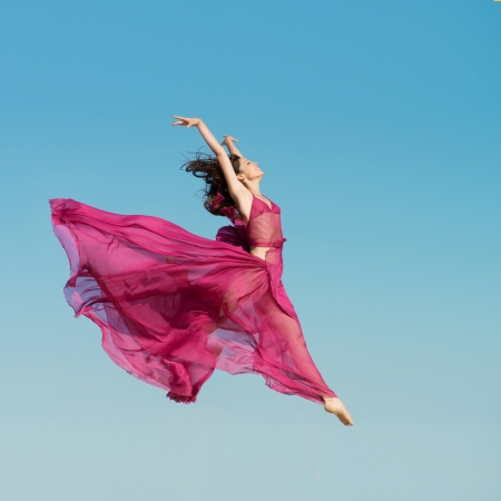 Woman in air red dress jumping in the air Imagens