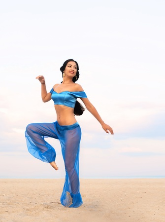 Full length portrait of a beautiful dancing girl in belly dance costume photo