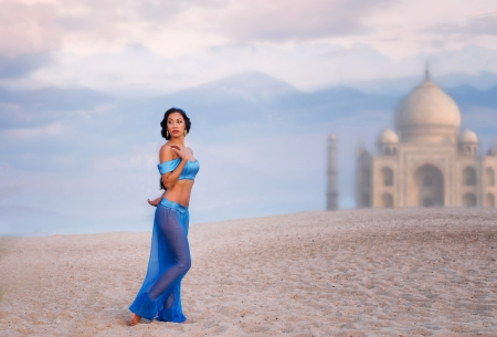 Full length portrait of a beautiful girl in belly dance costume with an image of eastern palace in the distance