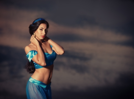 Eastern style portrait of a beautiful girl in belly dance costume at sunset photo