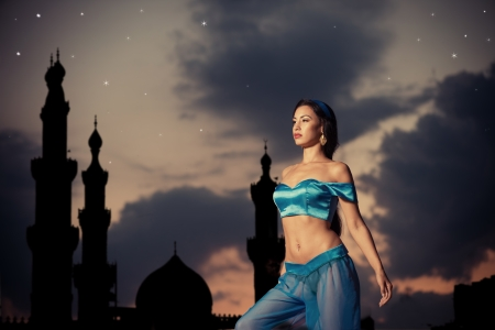 Arabian nights  Beautiful girl in belly dance costume with a silhouette of eastern palace in the starry sky