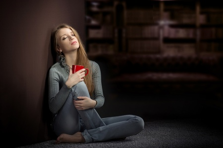 agreeable: Young woman with red cup sitting on the floor and dreaming