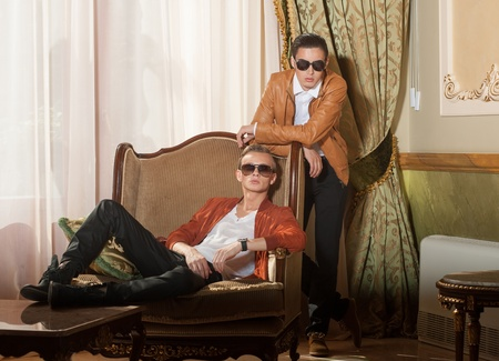 Indoors portrait of two young men in sunglasses Stock Photo