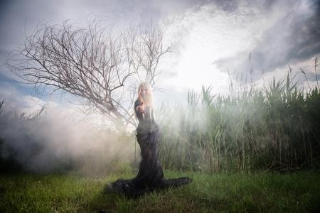 se�al de silencio: Figura femenina extra�a en negro haciendo se�as a alguien de la niebla de la ma�ana Foto de archivo