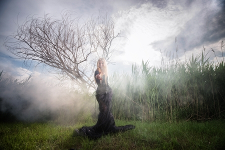 Weird female figure in black beckoning someone from the morning mist