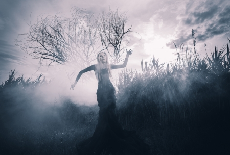 Demonic female figure in the fog, monochromatic shot
