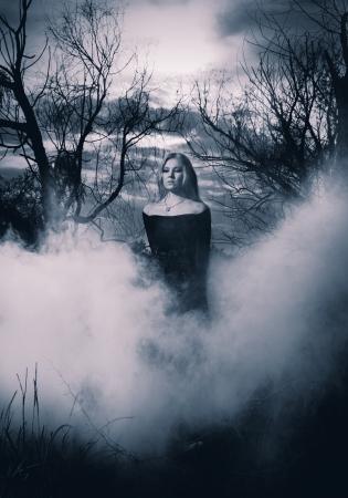 fille triste: Femme en noir debout dans le brouillard, monochromatique abattu Banque d'images