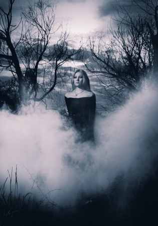 Woman in black standing in the fog, monochromatic shot Stock Photo