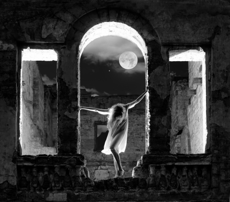 Mysterious female figure standing in the arc of the ruined building in full moon night, black and white shot