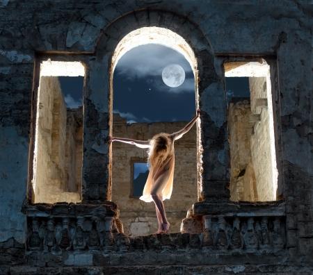 Mysterieuze vrouwelijke figuur staan in de boog van de verwoeste gebouw in volle maan 's nachts