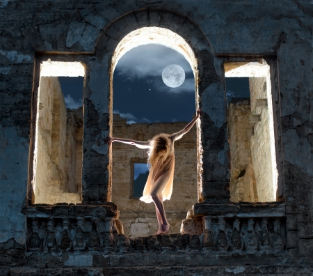 Mysterious female figure standing in the arc of the ruined building in full moon night photo