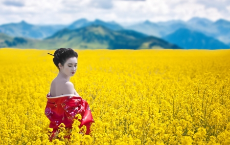 Asian style portrait of a woman with bare shoulders looking back in the yellow flowering field, mountains background