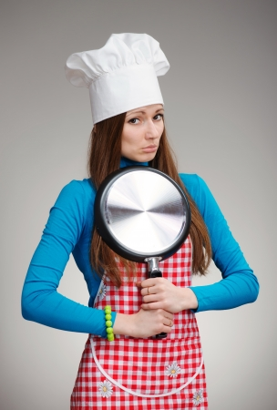 Funny portrait of a woman in chef s hat with the pan in her hands