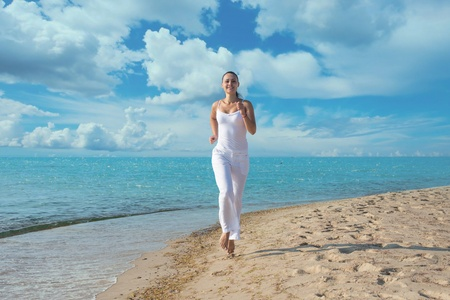 running pants: Happy young woman in white clothes running on the beach Stock Photo