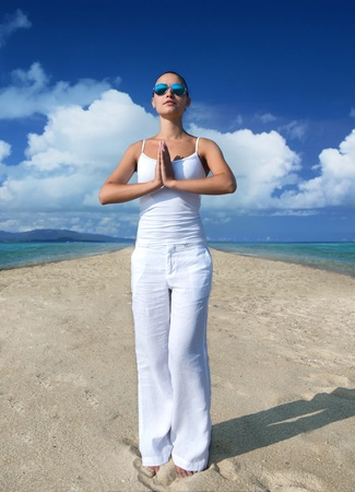 rest in peace: Young woman in white clothes meditating on the beach Stock Photo