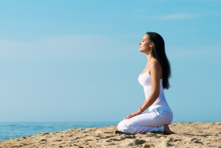 Young woman in white clothes meditating on the beach, portrait in profile photo