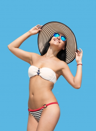 Portrait of a happy woman in bikini and the big stripy hat, blue sky background Stock Photo