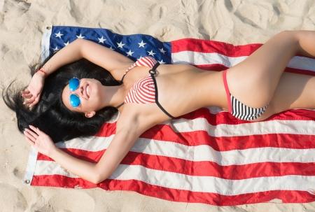 bandera estados unidos: Chica linda morena en bikini y gafas de sol azules que mienten en la bandera americana en la playa de arena, vista desde arriba Foto de archivo
