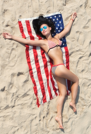 Pretty brunette girl in bikini lying on the American flag on the sand beach, view from above photo