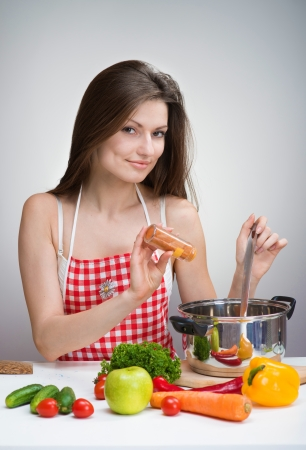 Pretty smiling woman in an apron seasoning soup with paprika photo