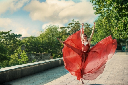 transparent dress: Romantic portrait of the woman in airy red dress dancing on the boulevard Stock Photo