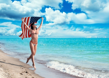 Happy girl in bikini running on the beach with the American flag fluttering in her hands