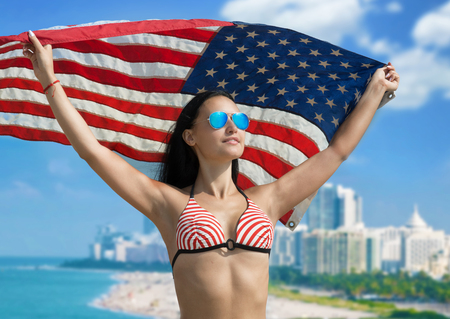 Portrait of a smiling girl in bikini with the American flag fluttering in her hands photo