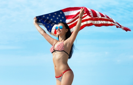 Portrait of a smiling young woman in bikini with the American flag fluttering in her hands, blue sky background photo